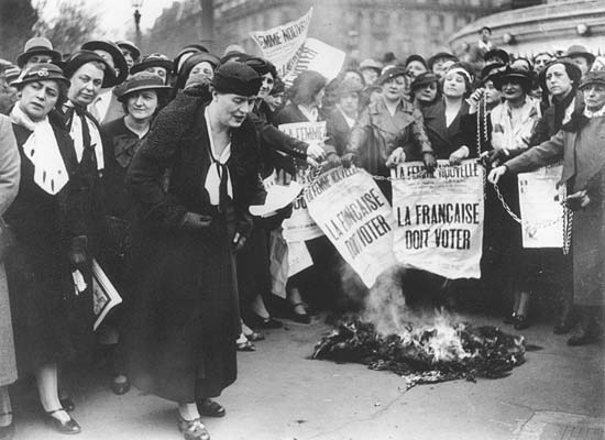 Louise Weiss along with other suffragettes in 1935. The bold text on the newspaper reads 'The Frenchwoman must vote'.